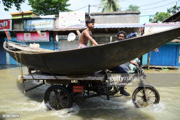 People transport a boat on a motorbike to use in the flood affected area in Shehagori village around 40km west of Kolkata on July 28 2017 The Indian...