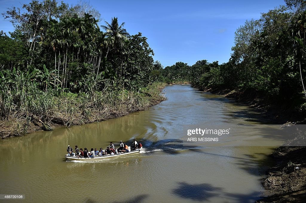 People travel by boat on a river near the village of Tora in the jungle of Papua New Guinea on September 9 2014 AFP PHOTO / ARIS MESSINIS