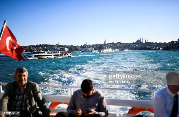 TOPSHOT People travel by ferry boat on the Bosphorus after it has turned turquoise due to phytoplankton on June 14 in Istanbul The Moderate...