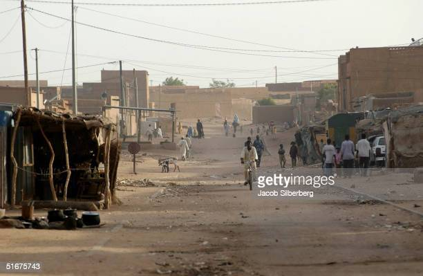 People travel on a street lined with hostels for migrants who are trying to cross the Sahara but become waylaid on September 24 2004 in Agadez Niger...