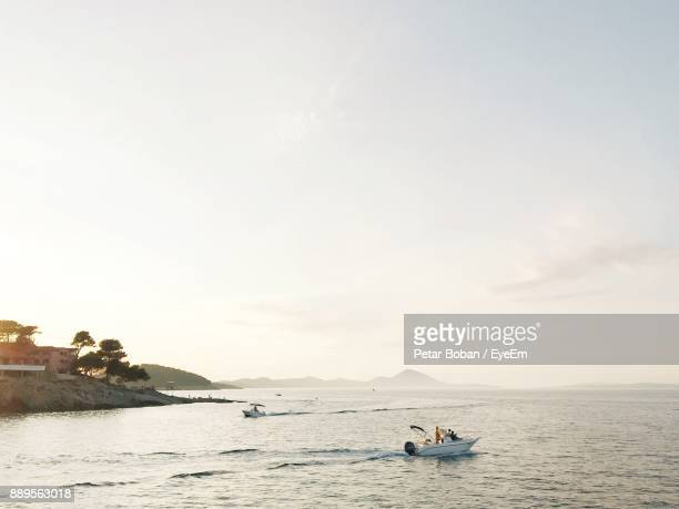 People Traveling In Boat On Sea Against Sky
