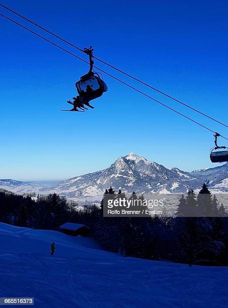 People Traveling In Ski Lift Over Snow Covered Landscape Against Sky
