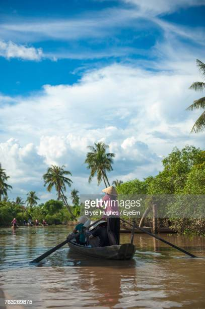 People Traveling On Boat In River Against Sky
