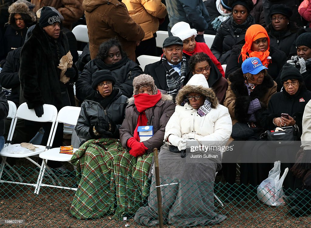 People try and stay warm before the presidential inauguration on the West Front of the U.S. Capitol January 21, 2013 in Washington, DC. Barack Obama was re-elected for a second term as President of the United States.