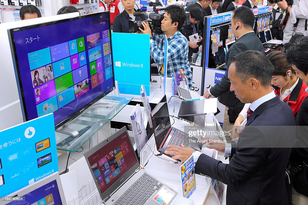 People try computers carrying Windows 8, the new operating system of Microsoft at an electric shop on October 26, 2012 in Tokyo, Japan.