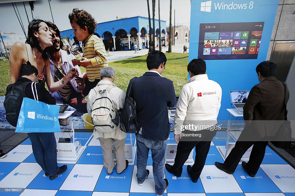 People try out tablet devices and laptop computers running Microsoft Corp.'s Windows 8 operating system outside an electronics store in Tokyo, Japan, on Friday, Oct. 26, 2012. Microsoft introduced the biggest overhaul of its flagship Windows software in two decades, reflecting the rising stakes in its competition with Apple Inc. and Google Inc. for the loyalty of customers who are shunning personal computers and flocking to mobile devices. Photographer: Kiyoshi Ota/Bloomberg via Getty Images