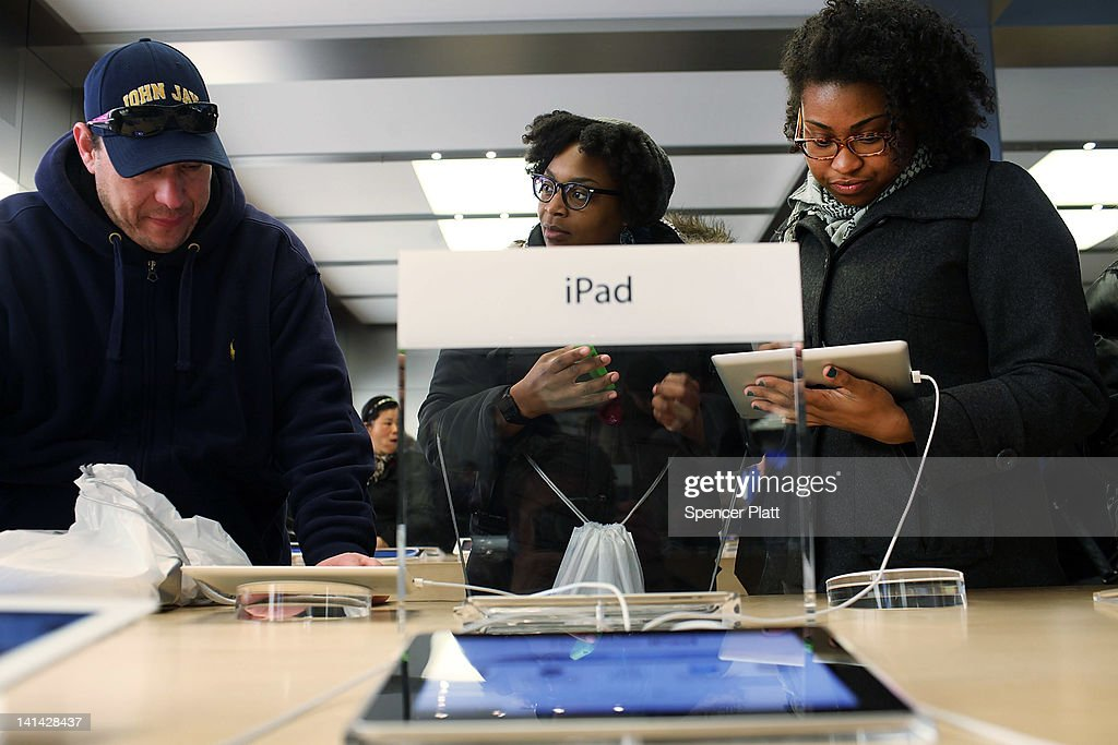 People try the new iPad on the first day it went on sale around the world March 16, 2012 in New York City. Simply called the iPad, the new tablet replaces the iPad 2 and features a high-pixel-count 'retina display.' Hundreds of people waited in line all night to be the first into the flagship Apple Store on Manhattan's Fifth Avenue.