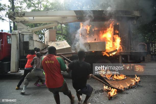 TOPSHOT People try to carry refrigerators off a truck that was set on fire by demonstrators during a protest against the remobilisation of the army...