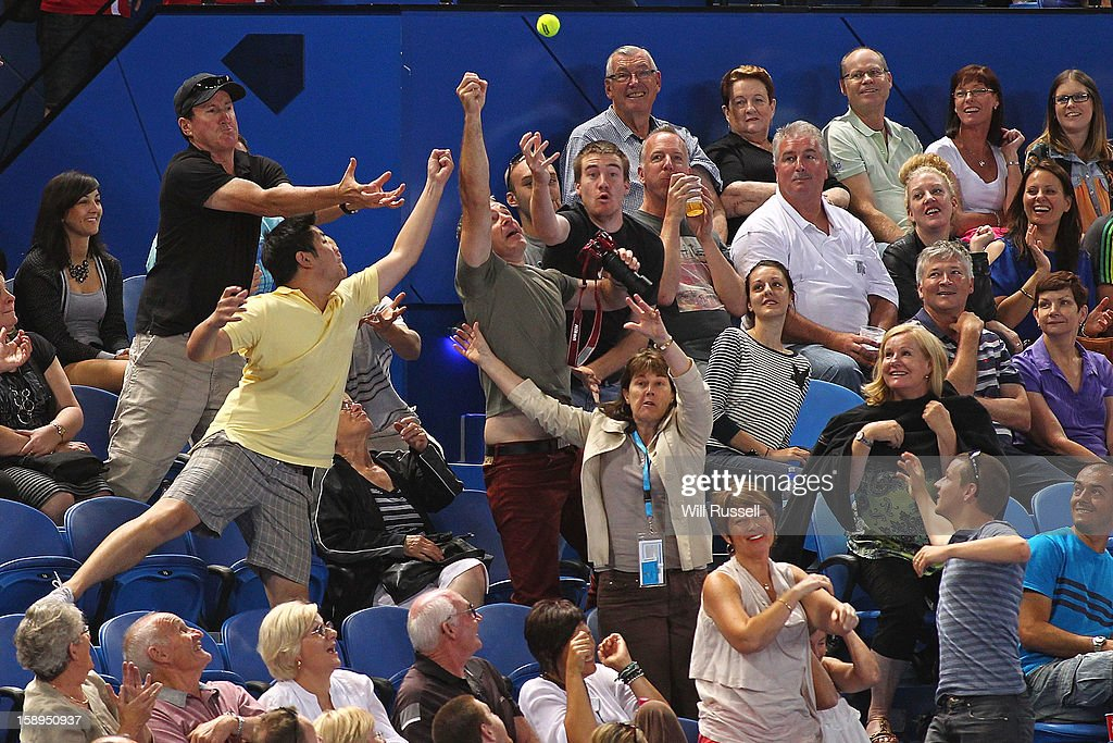 People try to catch a tennis ball hit into the crowd but Novak Djokovic during his mixed doubles match against Tatjana Malek and Thanasi Kokkinakis of Germany day seven of the Hopman Cup at Perth Arena on January 4, 2013 in Perth, Australia.