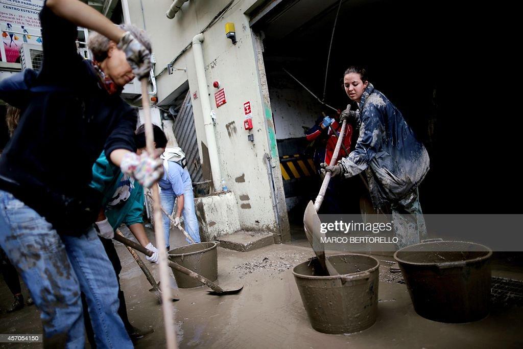 People try to clear of the mud downtown Genoa on October 11 2014 after one person died the day before when flood waters swept through the city...