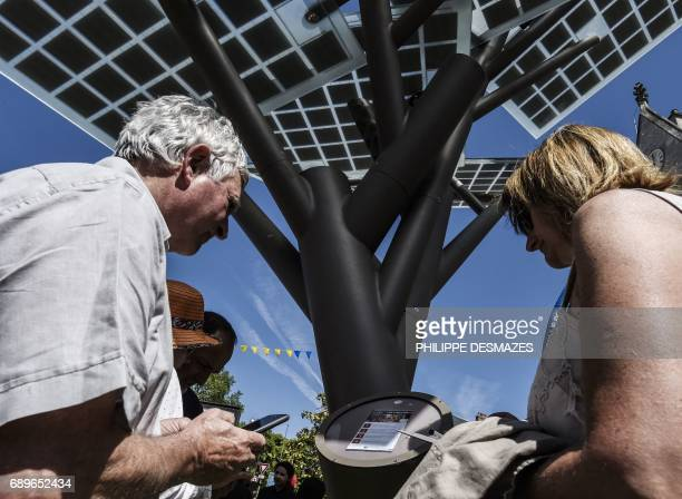 People try to connect their smartphones to the first 'eTree' provided in Europe by Solar Tree Europ a FrenchIsraeli start up on May 29 during an...