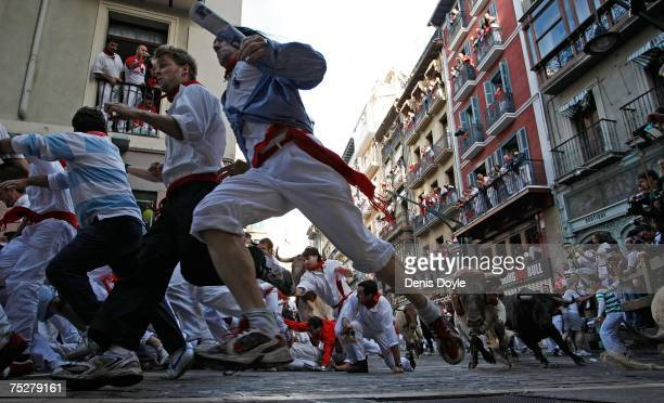 People try to evade fighting bulls during the fourth day of the San Fermin running of the bulls fiesta on July 9 2007 in Pamplona Spain Crowds run...