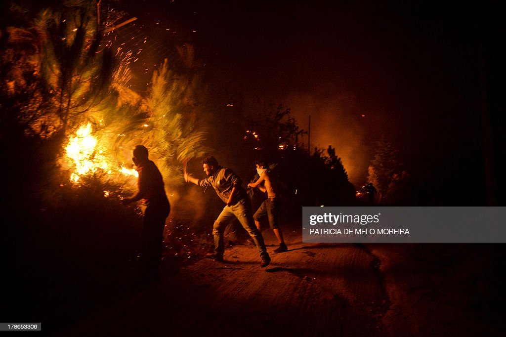 People try to extinguish a wildfire approaching their houses in Santiago de Besteiros, near Caramulo, central Portugal, early on August 30, 2013. Five Portuguese mountain villages were evacuated overnight as forest fires intensified in the country's north and centre, officials said today. As many as 1,400 firefighters were dispatched Thursday to tackle the blaze in the mountains and another raging further north in the national park of Alvao, where 2,000 hectares (4,900 acres) of pine forest have already been destroyed, according to the local mayor.