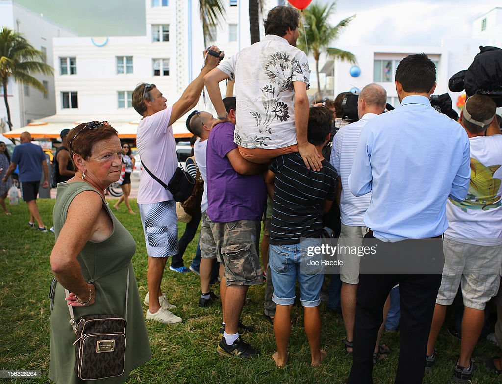 People try to get a glimpse of John McAfee as he speaks with reporters outside of the Beacon Hotel where he is staying after arriving last night from Guatemala on December 13, 2012 in Miami Beach, Florida. McAfee is a 'person of interest' in the fatal shooting of his neighbor in Belize and turned up in Guatemala after a month on the run in Belize.