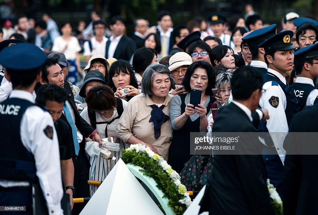 People try to get a glimpse of the wreath laid by US President Obama at the Hiroshima Peace Memorial park cenotaph in Hiroshima on May 27, 2016. Obama became the first sitting US leader to visit the site that ushered in the age of nuclear conflict. / AFP / JOHANNES