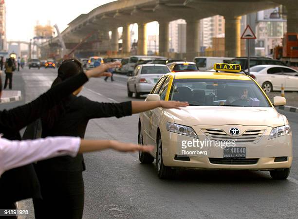 People try to hail a taxi in Dubai United Arab Emirates on Thursday May 22 2008 About 6000 taxis and 500 buses serve more than six million business...