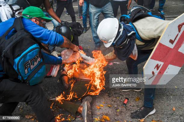 TOPSHOT People try to help a fellow demonstrator who catched fire after the gas tank of a police motorbike exploded during clashes in a protest...