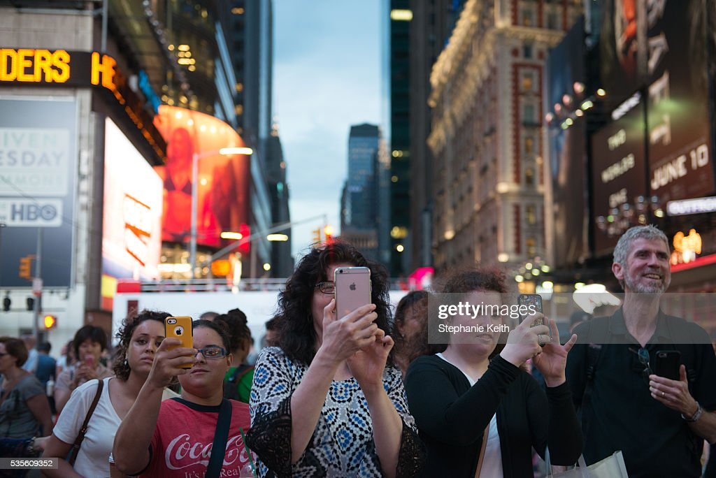 People try to take a photo of Manhattanhenge, which was not visible due to clouds, on May 29, 2016 in New York City. Manhattanhenge, an event that happens twice a year, occurs when the setting sun aligns with the east-west streets of Manhattan.