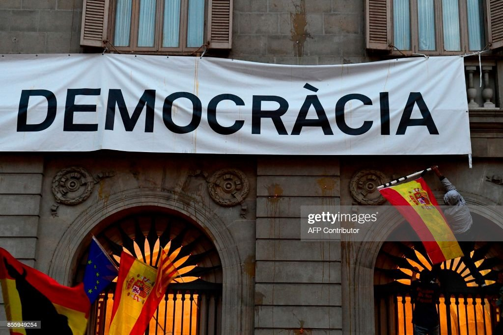 People try to take down a banner reading 'Democracy' during a demonstration against independence in Catalonia, on September 30, 2017 in Barcelona. Hundreds of people, many waving red and yellow Spanish flags, rallied in Barcelona in favour of Spanish unity today, a day before a banned independence referendum in Catalonia. /