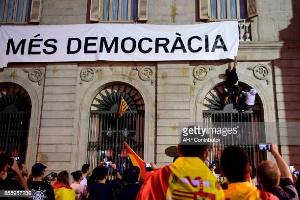 People try to take down a banner reading 'More Democracy' during a demonstration against independence in Catalonia on September 30 2017 in Barcelona...