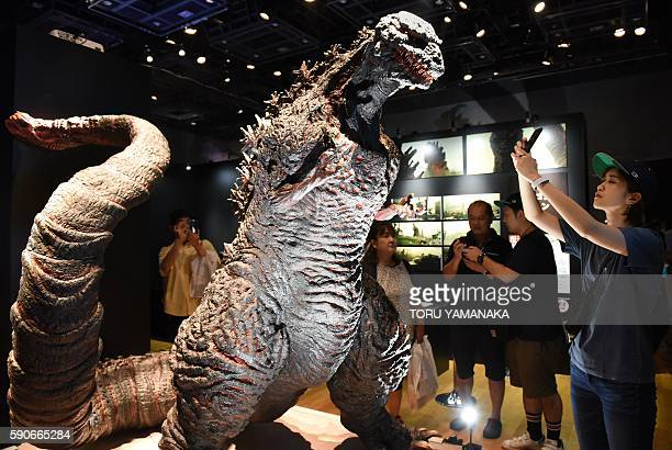People try to take pictures of Godzilla at the Godzilla exhibition in Yokohama suburb of Tokyo to promote latest movie of the monster released in...