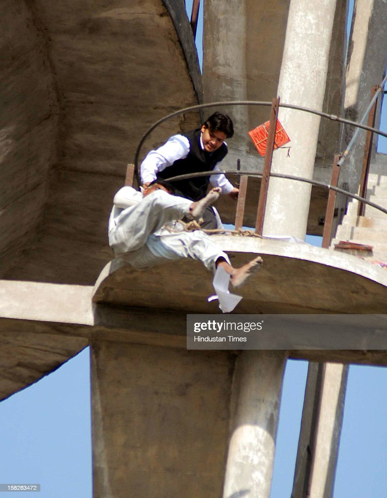 People trying to catch a 38 year old man who jumped off from a water-tank at Vijay Nagar as police and locals looked on, Victim was later declared dead on December 12, 2012 in Ghaziabad, India.