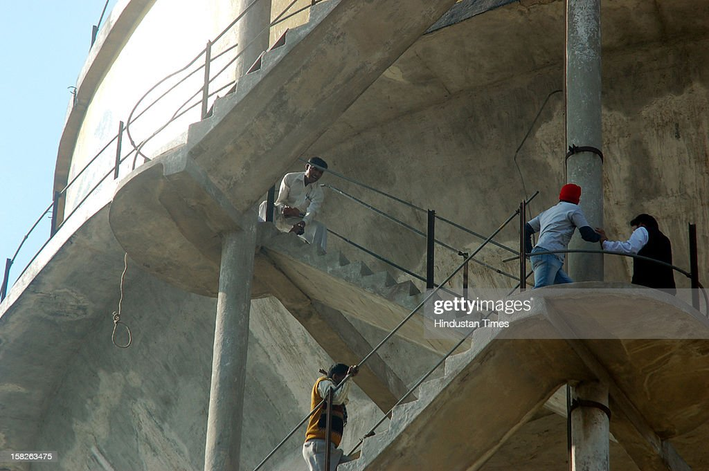 People trying to stop a 38 year old man who jumped off from a water-tank at Vijay Nagar as police and locals looked on, v ictim was later declared dead on December 12, 2012 in Ghaziabad, India.