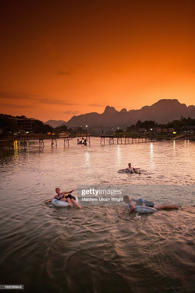People tubing downriver at sunset. : Stock Photo