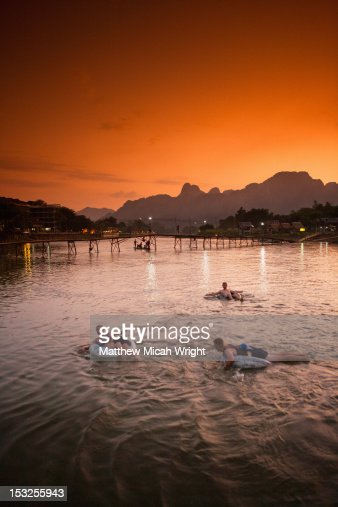People tubing downriver at sunset. : Stock-Foto