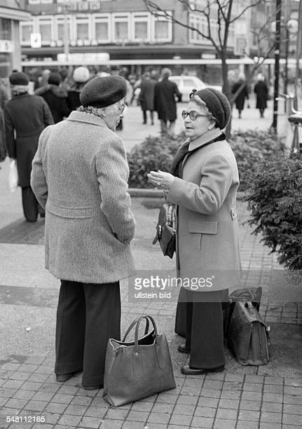 people two older women in a conversation on the street shopping bags aged 70 to 80 years