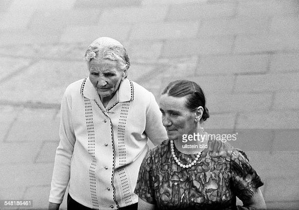 people two older women in a pedestrian zone aged 65 to 80 years