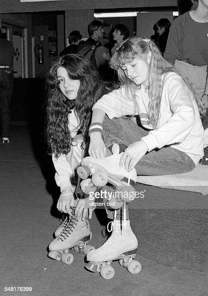 people two young girls sit side by side and put on their rollerblades jeans trousers pulli aged 15 to 18 years