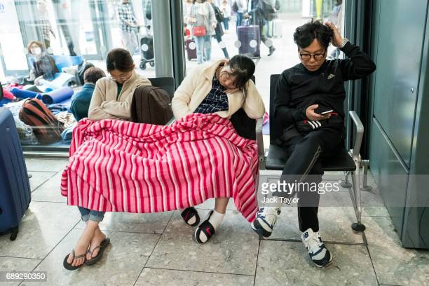 People under a blanket sleep on chairs at Heathrow Airport Terminal 5 on May 28 2017 in London England Thousands of passengers face a second day of...