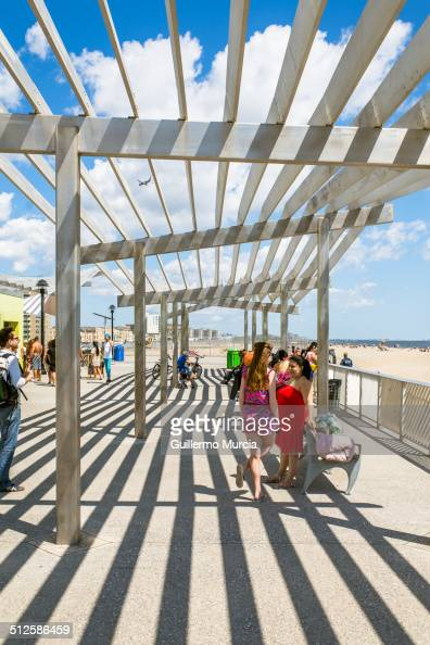 People under the canopy of the 109th street Rockaway Beach station and boardwalk Queens New York August 24 2014