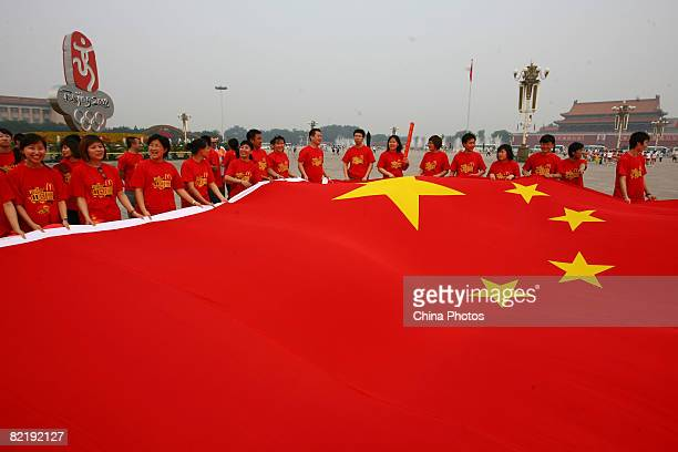 People unfold a huge China's national flag during the Beijing leg of Olympic torch relay on August 6 2008 in Beijing China The games commence on...