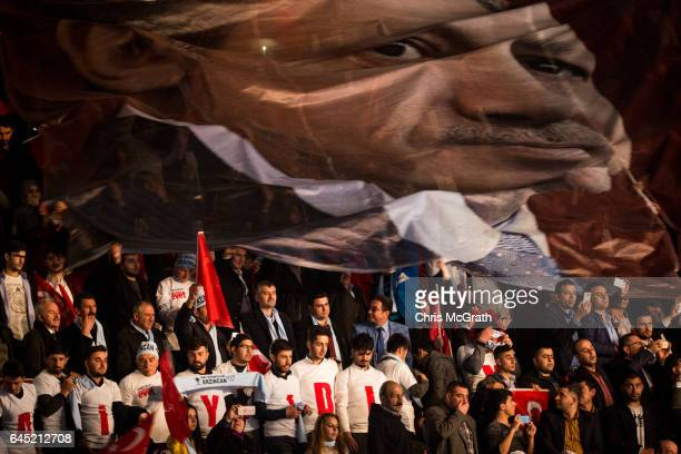 People unfurl a large banner of President Recep Tayyip Erdogan during a rally officially opening the AKP Party 'Yes' constitutional referendum...