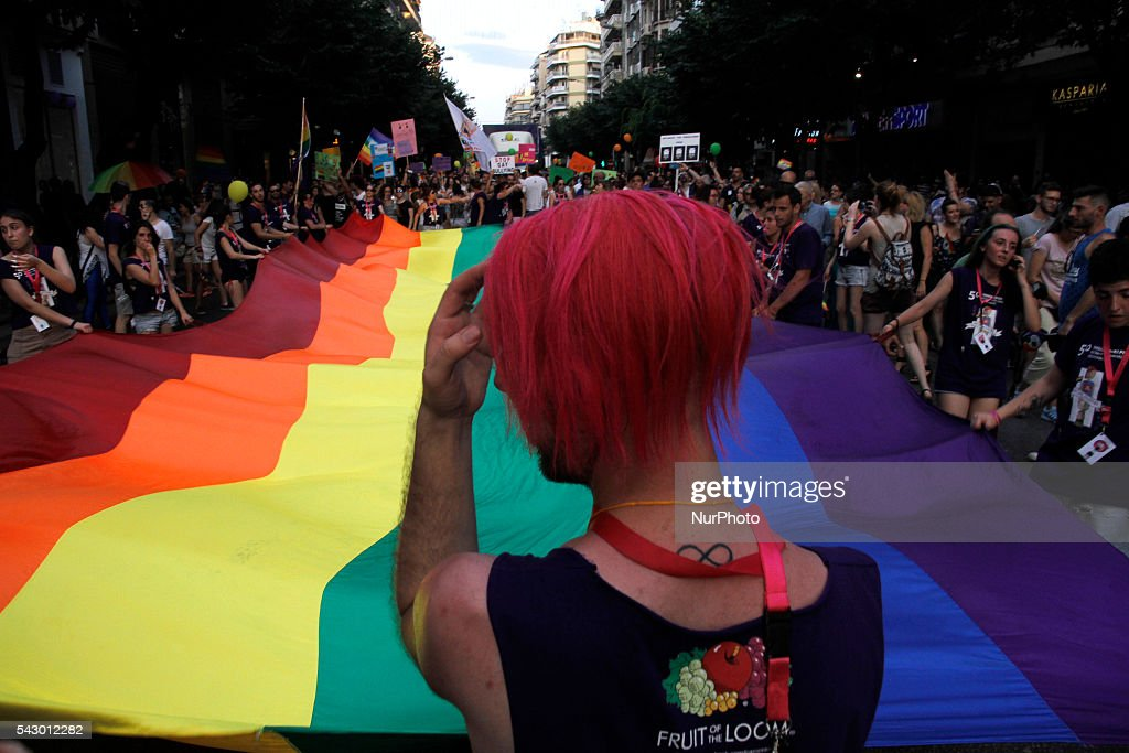 People unfurl a Peace flag as they parade in the streets of Thessaloniki, northern Greece, taking part in the city's 4th Gay Pride march, on June 25, 2016.