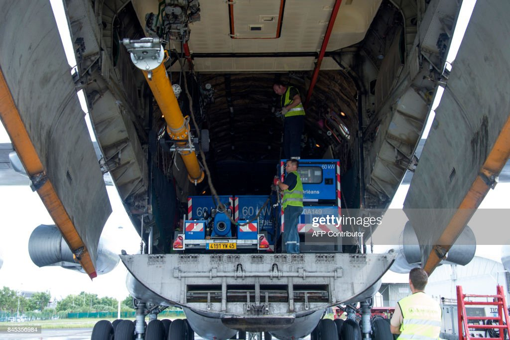 People unload a Ilyushin 76 airplane carrying EDF material (including power generators and transformer units) for the French Caribbean islands of Saint Martin and Saint Barthelemy after the passage of Hurricane Irma, after it landed at the Pointe-a-Pitre International Airport in Les Abymes, on the French Caribbean island of Guadeloupe. Ravaged by Hurricane Irma, Saint Martin and Saint Barts escaped a further battering by Jose, which had 'markedly less' of an impact on the two Caribbean islands than anticipated, France's meteorological agency said on September 10. / AFP PHOTO / Helene Valenzuela