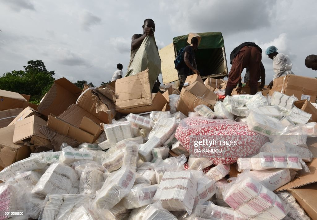 People unload fake medecine at the cemetery of Abobo district of Abidjan to be incinerated on March 10, 2017. 50 tonnes of fake medicine, for an estimated value of more than 1 million euros, were burnt in Abidjan on March 10, 2017. / AFP PHOTO / Sia KAMBOU