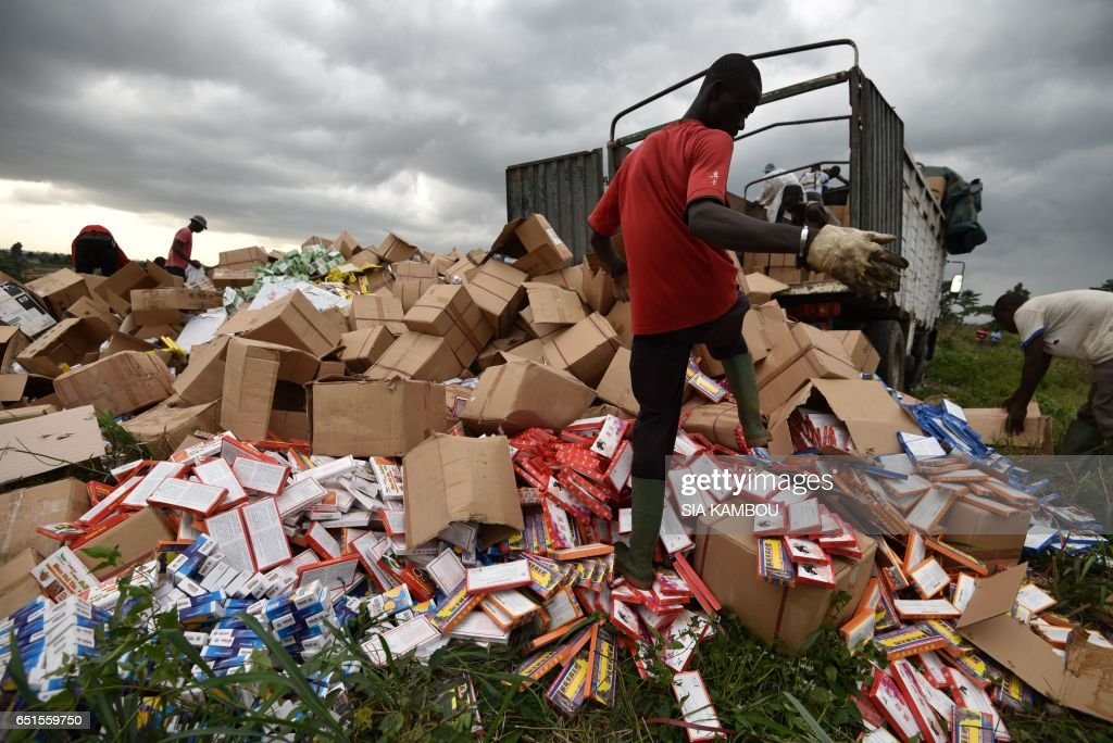People unload fake medecine to be incinerated at the cemetery of Abobo district of Abidjan on March 10, 2017. 50 tonnes of fake medicine, for an estimated value of more than 1 million euros, were burnt in Abidjan on March 10, 2017. / AFP PHOTO / Sia KAMBOU
