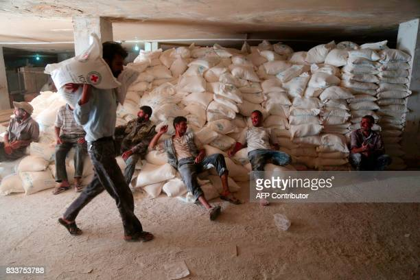 People unload supplies from a Syrian Arab Red Crescent truck in the rebelheld town of Douma on the eastern outskirts of Damascus on August 17 2017 /...