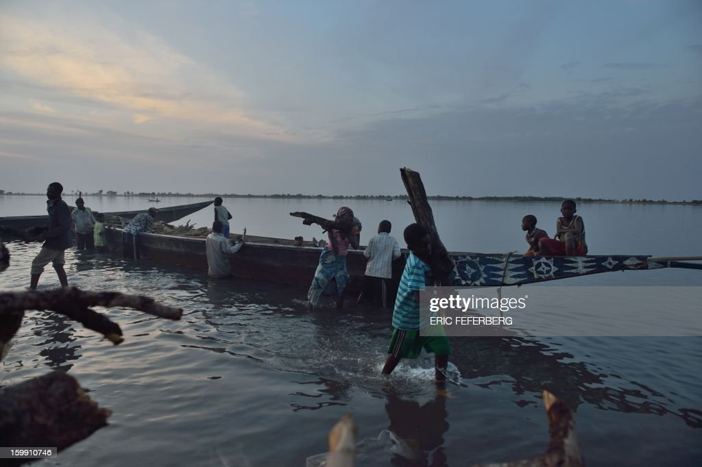 People unload wood from a boat on the Niger river on January 22, 2013 in Segou, 240 kms north of Bamako, as life starts returning to normal following the French-led offensive in Mali. Mali's army chief said on January 22 that his French-backed forces could reclaim the northern towns of Gao and fabled Timbuktu from Islamists in a month, as more offers of aid poured in for the offensive. French planes bombed a major base of the Al-Qaeda in Islamic Maghreb (AQIM) near Timbuktu as local sources said a mansion belonging to Libyan former strongman Moamer Kadhafi was destroyed. AFP PHOTO / ERIC FEFERBERG