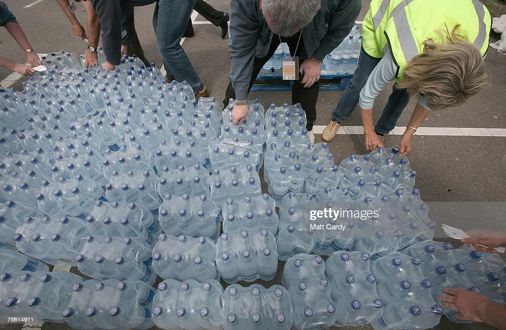 People unwrap water bottles as they are delivered at an emergency water collection point in Tesco's car park on July 24 2007 in Gloucester England...