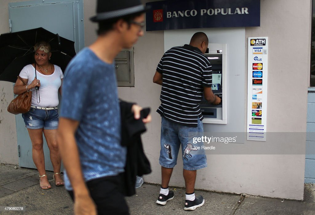 People use a Banco Popular ATM machine a day after Puerto Rican Governor Alejandro Garcia Padilla gave a televised speech regarding the governments...