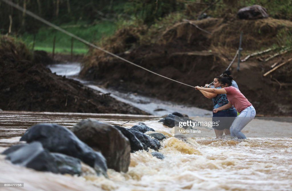 People use a rope line to cross the San Lorenzo de Morovis river more than two weeks after Hurricane Maria hit the island on October 6, 2017 in San Lorenzo, Puerto Rico. Flooding from the hurricane destroyed the bridge and San Lorenzo residents are forced to cross the river on foot or in 4 x 4 vehicles. Less than 11 percent of Puerto Ricans have electricity currently and only 42 percent have working phones. Puerto Rico experienced widespread damage including most of the electrical, gas and water grid as well as agriculture after Hurricane Maria, a category 4 hurricane, swept through.
