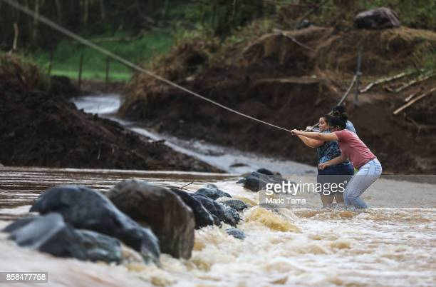 People use a rope line to cross the San Lorenzo de Morovis river more than two weeks after Hurricane Maria hit the island on October 6 2017 in San...