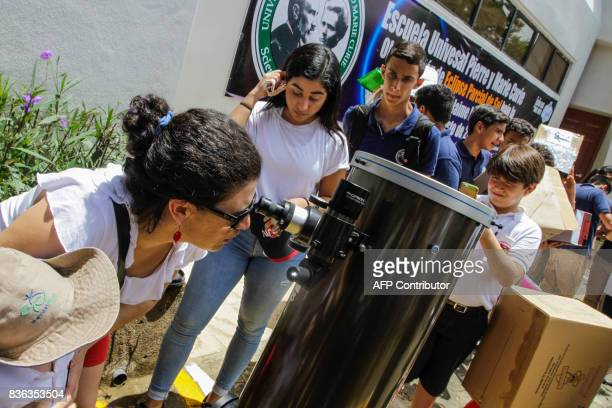 People use a telescope to view the 30 percent solar eclipse that was seen in Managua on August 21 2017 / AFP PHOTO / INTI OCON
