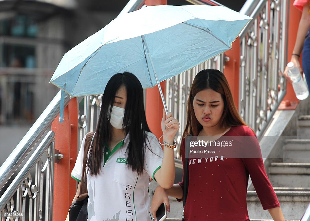 People use an umbrella to protect themselves from the sun at Victory Monument neighborhood, where the Meteorological Department announced that the temperature ranges from 34-39 degrees Celsius.