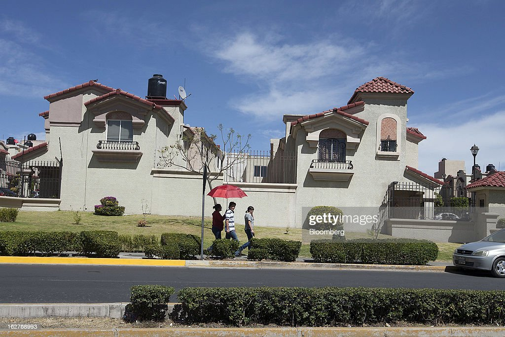 People use an umbrella to shade themselves from the sun as they walk in the Urbi Desarrollos Urbanos SAB's Urbi Quinta Montecarlo housing development in Cuautitlan Izcalli, Mexico, on Monday, Feb. 25, 2013. Urbi Desarrollos Urbanos SAB, the Mexican homebuilder that lost three-fourths of its market value in the past year, will report negative free cash flow to equity for the fourth quarter of 2012, according to a company official with direct knowledge of the matter. Photographer: Susana Gonzalez/Bloomberg via Getty Images
