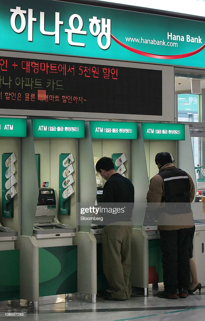 People use automatic teller machines (ATM) at a Hana Bank branch in Seoul, South Korea, on Thursday, Feb. 9, 2012. Hana Financial Group Inc. completed its 4.4 trillion won ($3.9 billion) purchase of Korea Exchange Bank from Lone Star Funds and Export Import Bank of Korea, allowing Hana to narrow a gap with rivals and the U.S. fund to exit the investment after eight years. Photographer: SeongJoon Cho/Bloomberg via Getty Images